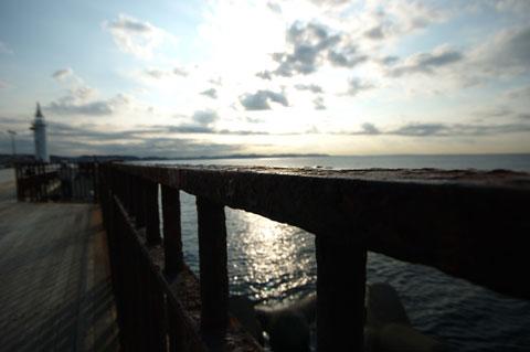 江ノ島の防波堤(の錆びた手すり)。ここは早朝から釣り人でにぎわいます。左奥は灯台です。