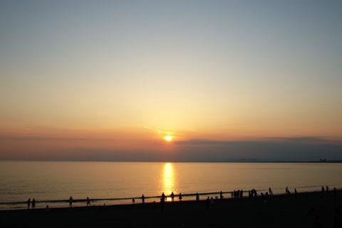 大勢の人達が,波打ち際で夕日を眺めています。