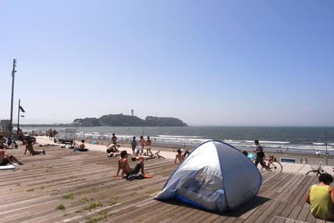 片瀬海岸のウッドデッキ。自転車に乗る人,本を読む人,日焼けをする人,キャンプする人(?)。ここはいつも自由でのんびりした時間が流れています。