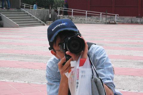 悪い例。お茶とガイドブック,ビデオカメラを持ちながら,デジ一眼で家族を撮るおいら (@首里城)