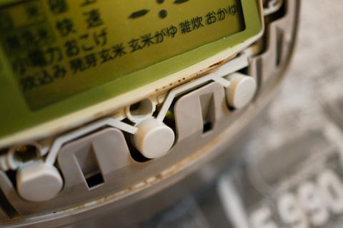 真ん中のボタンの右下に,僅かに見える黄色い物体がリチウム電池(のカバー)